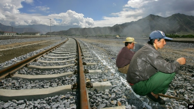FILE - Workers take a break sitting on the tracks leading to the platform of the train station in Lhasa, Tibet, China. First announced last week, the 1,800-kilometer (1,120-mile) line would link Lhasa with the western metropolis of Chengdu with an estimated travel time of 13 hours.