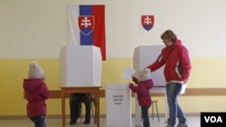 Seorang anak memasukkan surat suara ke dalam kotak suara di Bratislava, Slovakia (10/3).