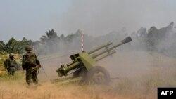 Des soldats des Forces armées de la République démocratique du Congo (FARDC) tirent une pièce d'artillerie mobile lors de l'opération Sokola 1 à Matombo, à 35 km au nord de Beni, au Nord-Kivu, le 13 janvier 2018..