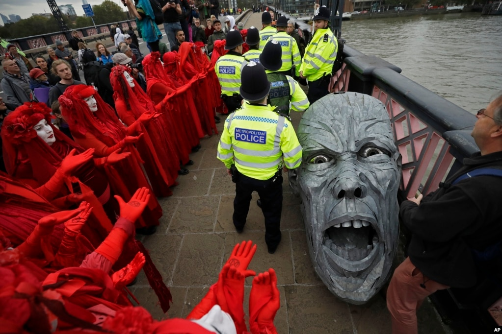 Environmental activists demonstrate around the head of a statue taken by police on Lambeth bridge in central London.