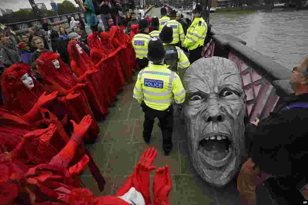 Environmental protesters gather around the head of a statue confiscated by police on Lambeth bridge in central London.