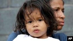 Jesús Funes, de 19 meses, es sostenido por su madre, Diva Funes, ambos inmigrantes de Honduras, tras ser esoltados de regreso a Reynosa, México, el jueves, 21 de junio de 2018. La familia, que buscaba asilo, fue advertida por funcionarios que si cruzaba ilegalmente sería separados por lo que decidieron retornar voluntariamente.