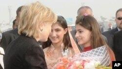 امریکی وزیر خارجہ ہلیری کلنٹن اپنے ایک حالیہ دورہ پاکستان میں پاکستانی لڑکیوں سے پھولوں کے گلدستے وصول کرتے ہوئے۔ فائل فوٹو