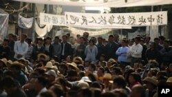 Residents of Wukan, a fishing village in the southern province of Guangdong, rally to demand the government take action over illegal land grabs and the death in custody of a local leader on December 15, 2011.