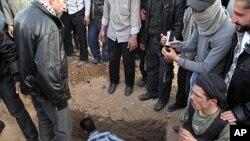 Một chiến binh của Đạo quân Syria Tự do ngồi cạnh huyệt của một đồng đội trong lễ mai táng 4 người bị thiệt mạng do cuộc đột kích của lực lượng chính phủ ở ngoại ô thủ đô Damascus, Syria