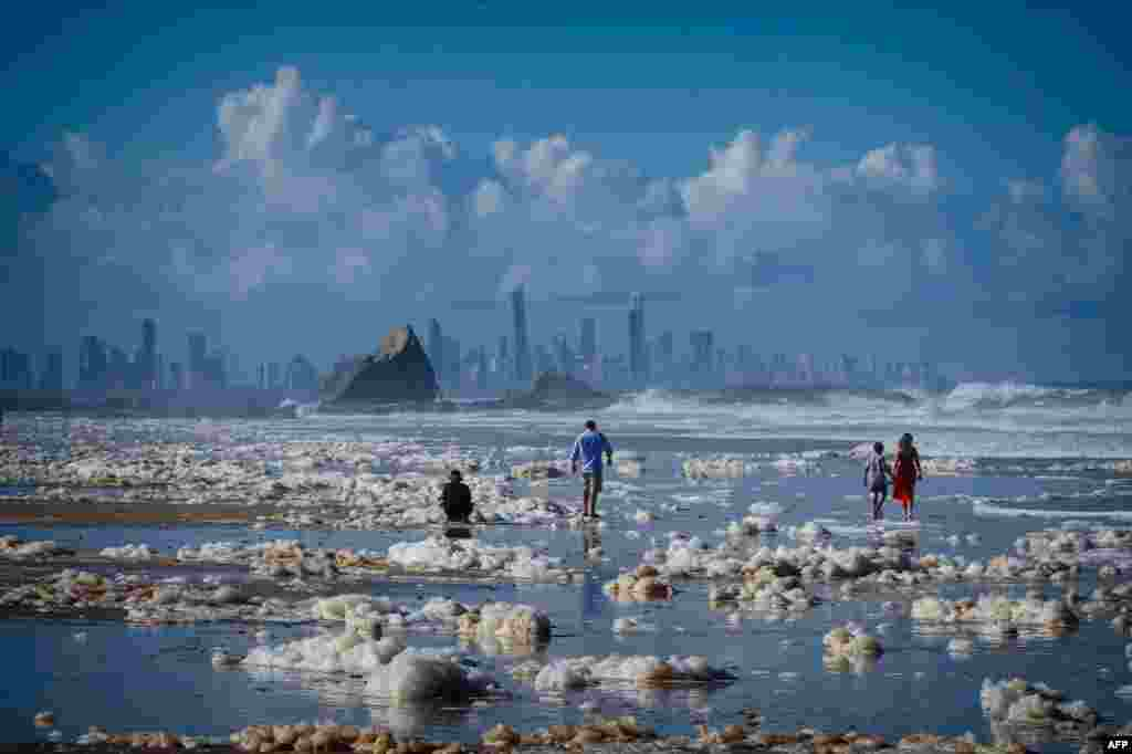 Tourists walk on the Currumbin Beach covered with foam in the wake of cyclonic conditions after wild weather lashed Australia's Northern New South Wales and South East Queensland with heavy rain, strong winds and king tides.