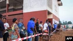 Les électeurs attendent pour voter devant un bureau de vote à Monrovia, le 8 décembre 2020