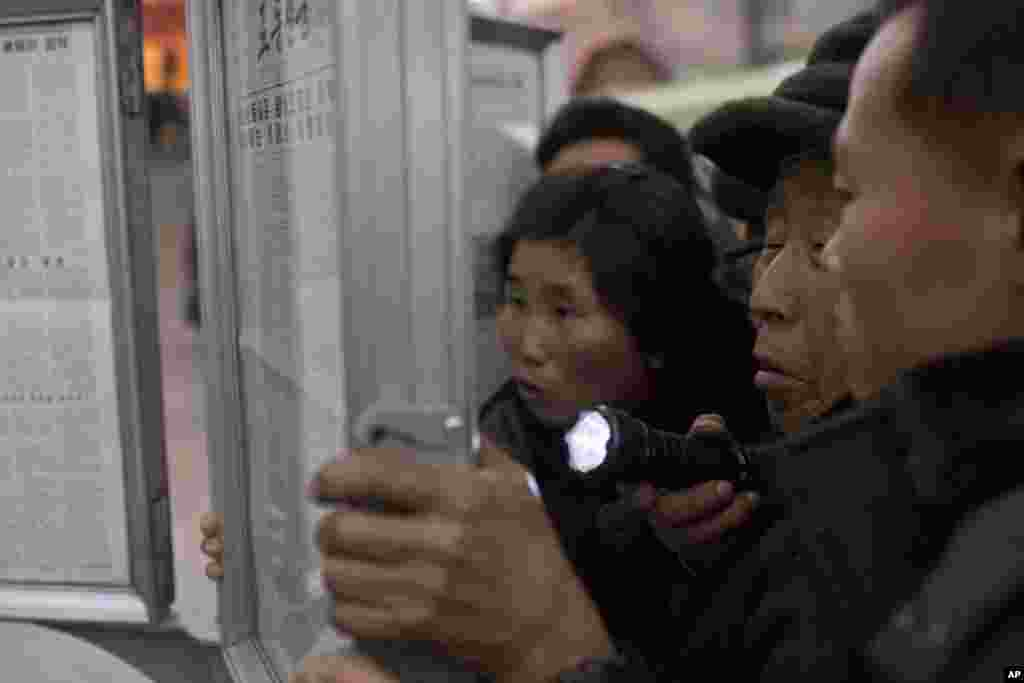 A North Korean man uses a flashlight as he and other subway commuters gather around a public newspaper stand on a train platform in Pyongyang to read headlines about Jang Song Thaek, North Korean leader Kim Jong Un's uncle, who was executed as a traitor.