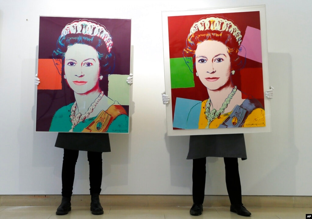 Gallery technicians display screenprints of Queen Elizabeth II by Andy Warhol, at Christie's auction rooms in London. The screenprints will be on sale online until March 31.