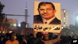 Một người biểu tình phản đối tại Quảng trường Tahrir, ở Cairo, Ai Cập, cầm bức ảnh ráp nối của Tổng thống đương quyền Morsi (phần trái) và cựu Tổng thống Mubarak. Công chúng tức giận vì ông Morsi và nhóm Huynh đệ Hồi giáo của ông nắm quá nhiều quyền hành