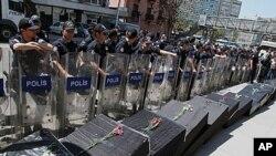 터키 수도 앙카라에서 쿠르드 반군에 대한 공습으로 사망한 34명을 나타내는 모형 관들 옆에 서있는 진압 경찰들(자료사진)