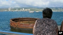 This Nov. 21, 2014 photo shows visitors looking out at the sunken USS Arizona from a memorial atop the rusting battleship in Pearl Harbor, Hawaii.