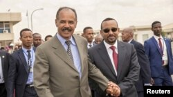 FILE - Eritrean President Isaias Afwerki and Ethiopia's Prime Minister Abiy Ahmed walk together at Asmara International Airport, Eritrea July 9, 2018.