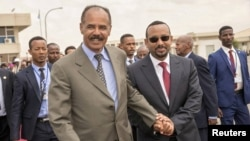 Eritrean President Isaias Afwerki and Ethiopian Prime Minister Abiy Ahmed walk together at Asmara International Airport, Eritrea, July 9, 2018. A peace deal between the East African neighbors garnered international commendations.