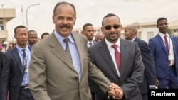 FILE - Eritrean President Isaias Afwerki and Ethiopia's Prime Minister Abiy Ahmed walk together at Asmara International Airport, Eritrea, July 9, 2018.