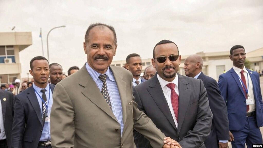 FILE - Eritrean President Isaias Afwerki, left, and Ethiopian Prime Minister Abiy Ahmed walk together at Asmara International Airport, Eritrea, July 9, 2018.