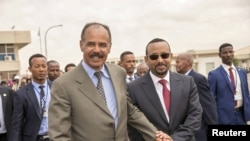 FILE - Eritrean President Isaias Afwerki, left, and Ethiopian Prime Minister Abiy Ahmed walk together at Asmara International Airport, Eritrea, July 9, 2018.