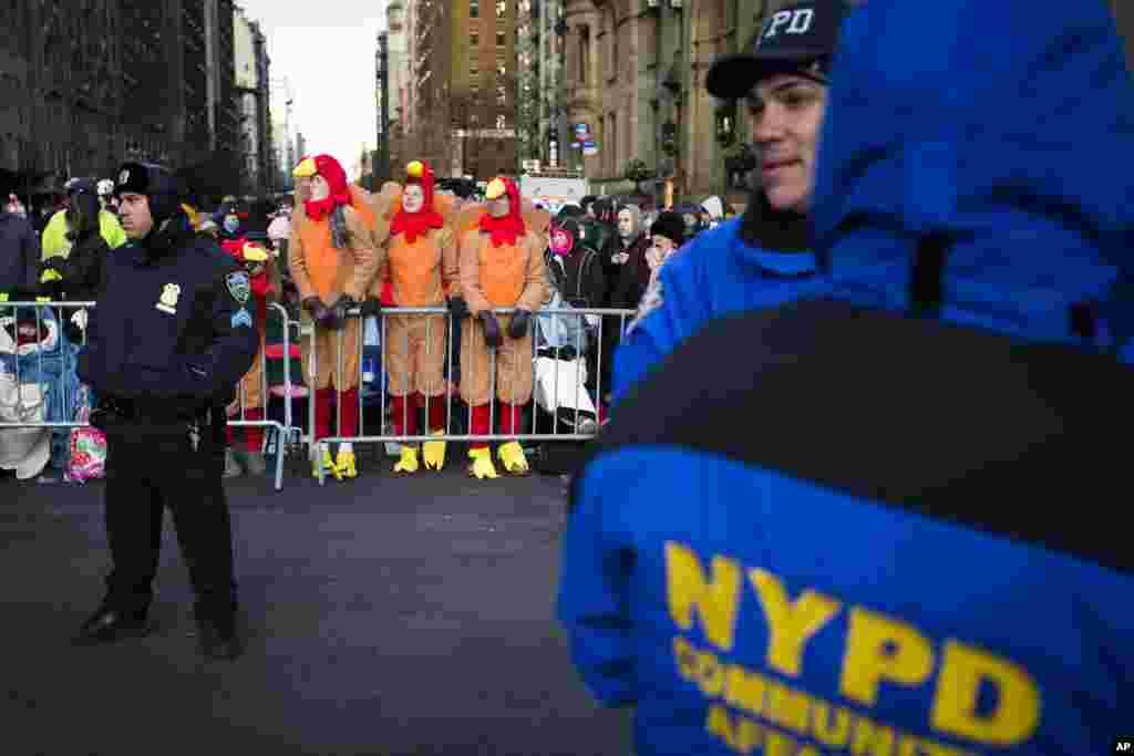 Para penonton memakai kostum kalkum berdiri di belakang barikade polisi saat menunggu Parade Hari Bersyukur Tahunan Macy's ke-87 di New York (28/11). (AP/John Minchillo)