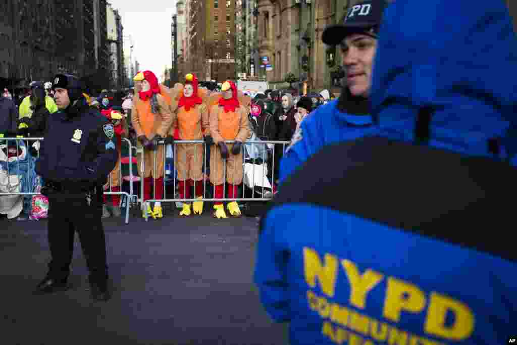 Spectators dressed as turkeys stand behind police barricades as they wait for the 87th Annual Macy's Thanksgiving Day Parade, New York, Nov. 28, 2013.