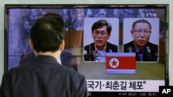지난 3월 한국 서울역에서 한 시민이 북한 당국에 체포돼 억류 중인 한국 국민 김국기(왼쪽)씨와 최춘길 씨에 관한 TV 보도를 시청하고 있다. (자료사진)