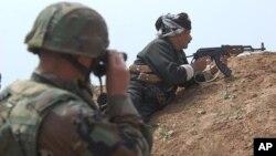 Tentara Amerika dengan binokularnya bersama tentara Kurdi di pinggiran kota Khazer, Irak utara. (Foto: Dok)