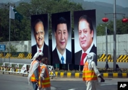 FILE - Municipality workers walk past a billboard showing pictures of Chinese President Xi Jinping, center, with Pakistan's President Mamnoon Hussain, left, and Prime Minister Nawaz Sharif on display during a two-day visit by the Chinese president to launch an ambitious economic corridor linking Pakistan's port city of Gwadar with western China, in Islamabad, Pakistan, April 20, 2015.