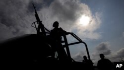 Military personnel are silhouetted while keeping watch at the perimeter of an area evacuated because of a gas leak caused by a pipeline theft in Puebla, Mexico, Sept. 12, 2018. A similar presumed fuel theft in 2017 left 10 dead and 13 detained with excessive force by the military, which is accused of human rights violations.