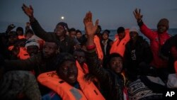 Migrants and refugees from different African nationalities sailing adrift on an overcrowded rubber boat, receive life jackets from aid workers of the Spanish NGO Open Arms in the Mediterranean Sea, international waters, off the Libyan coast, Friday,…