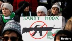 Učesnici marša na Vašington - zagovornici veće kontrole oružja u SAD nose transparent sa podsećanjem na tragediju u osnovnoj školi Sendi Huk.