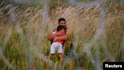 A migrant holds his child on the Serbian side of the fence in Asotthalom, Hungary, Sept. 15, 2015.