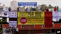 Cambodian non-governmental organization (NGOs) activists shout slogans during a protest against a proposed Don Sahong dam, in a tourist boat along the Tonle Sap river, in Phnom Penh, file photo.