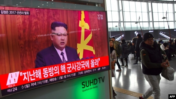 People walk past a television news broadcast at a railway station in Seoul on Jan. 1, 2017, showing North Korean leader Kim Jong-Un's New Year's speech.
