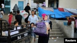 A family leaves a United Nations-run school sheltering displaced Palestinians, before making their way home after a ceasefire was declared, in the southern Gaza Strip, Aug. 27, 2014.