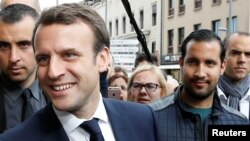 FILE - Emmanuel Macron, left, campaigns for the 2017 presidential election, flanked by Alexandre Benalla, right, head of security, in Rodez, France, May 5, 2017.