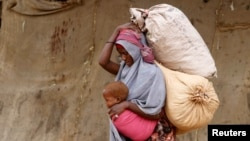 A displaced Somali woman carries a child and her belongings as she arrives at a temporary dwelling after fleeing famine in the Marka Lower Shebbele regions to the capital Mogadishu, Sept. 20, 2014. (REUTERS/Feisal Omar)