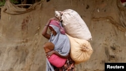 FILE - A displaced Somali woman carries a child and her belongings as she arrives at a temporary dwelling after fleeing famine in the Marka Lower Shebbele regions to the capital Mogadishu, Sept. 20, 2014. More recent shortages are linked to the El Nino weather phenomenon, which has proven to be one of the worst on record.