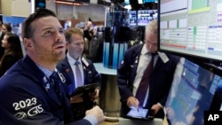 Specialist Frank Masiello, left, works at his post on the floor of the New York Stock Exchange, Nov. 7, 2016. Stocks opened sharply higher on Wall Street after the FBI said newly discovered emails didn't warrant any action against presidential candidate Hillary Clinton.