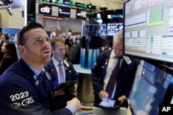 Specialist Frank Masiello, left, works at his post on the floor of the New York Stock Exchange, Nov. 7, 2016.