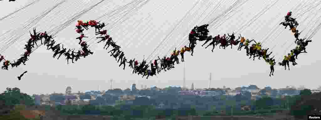"People jump off a bridge, which has a height of 30 meters, in Hortolandia, Brazil, Oct. 22, 2017. According to organizers, 245 people were attempting set a new world record for ""rope jumping"", in which people, tied to a safety cord, jump off a bridge."