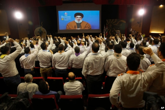 FILE - Hezbollah scouts raise their fists and cheer as they listen to a speech by Hezbollah leader Sayyed Hassan Nasrallah, via a video link, during an annual anniversary rally for Hezbollah al-Mahdi scouts, in southern Beirut, Lebanon, April 22, 2019.