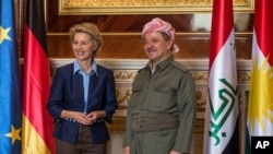 President of the Kurdish Autonomous Region in North Iraq Masoud Barzani, right, and German Defense Minister Ursula von der Leyen pose for media during their meeting in Erbil, Iraq, Sept. 25, 2014.