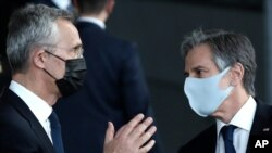 U.S. Secretary of State Antony Blinken, right, and NATO Secretary General Jens Stoltenberg wear protective masks as they prepare to stand with NATO foreign ministers for a socially distanced group photo during a meeting of NATO foreign ministers at…