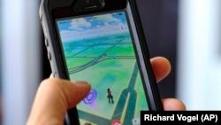 Seorang penggemar di Los Angeles dengan game Pokemon Go di ponselnya (foto: dok).