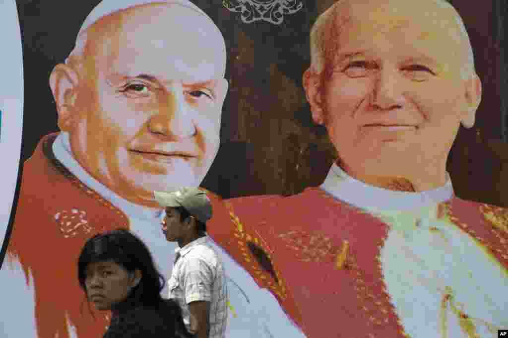 Dua orang berjalan di depan gambar Paus Yohanes ke-23, kiri, dan Paus Yohanes Paulus ke-2, Guatemala City, 27 April 2014.