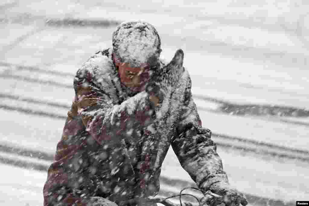 Fazendo ciclismo durante um nevão em Yantai, na China.