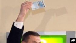 安西普总理高举从自动取款机中取出的欧元