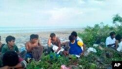 Wasu jama'a da ke kyautata zaton 'yan kabilar Rohingya ne yayin da wani kwalekwale ya sauke su a gabar ruwan kasar Malaysia