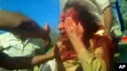 ທ່ານ Moammar Gadhafi ຖືກຫ້ອມລ້ອມ ໄປດ້ວຍພວກນັກຕໍ່ສູ້ ໃນເມືອງ Sirte ຂອງລີເບຍພາບຖ່າຍໃນທີ 20 ຕຸລາ, 2011