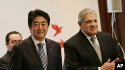 Japanese Prime Minister Shinzo Abe and Egyptian Prime Minister Ibrahim Mahlab arrive at a joint meeting of the Japan-Egypt business committee in Cairo, Egypt, Saturday, Jan. 17, 2015.