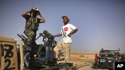 A former rebel fighter looks through binoculars as he stands in a convoy of revolutionary forces, moments before heading to the frontline in Bani Walid, at a checkpoint in Wadi Dinar, Libya, September 16, 2011.